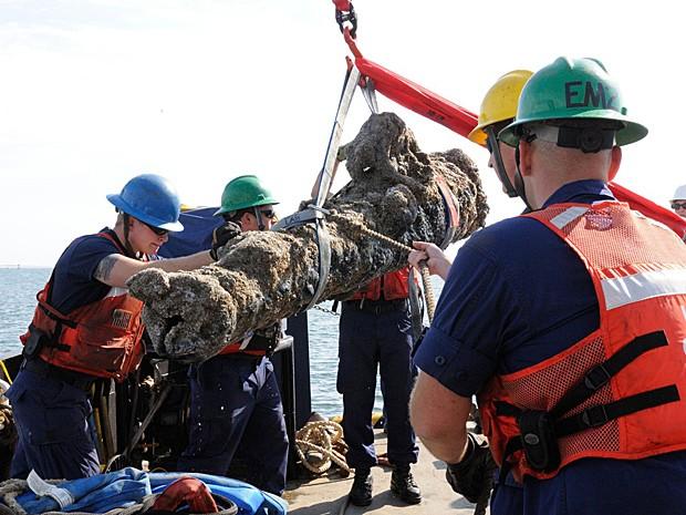 Membros da Guarda Costeira americana erguem um dos canhões recuperados de navio naufragado em 1718 na costa da Carolina do Norte (Foto: Karen A. Blum/NCDCR/AFP)