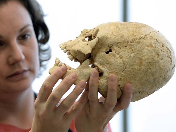 Pesquisadora de instituto de arqueologia francês trabalha no crânio deformado (Foto: FREDERICK FLORIN / AFP)